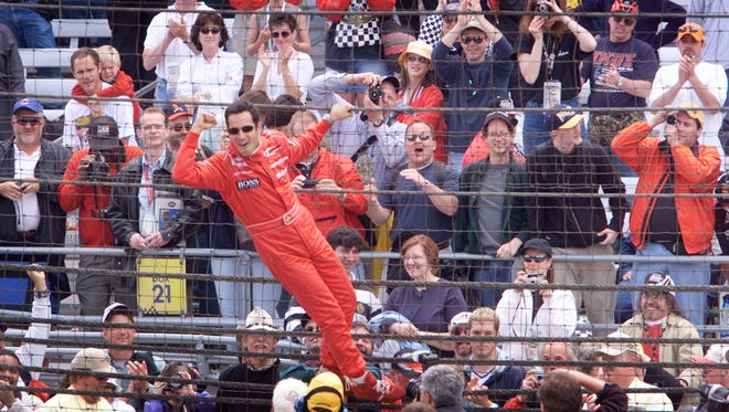Helio Castroneves climbs the fence to the delight of fans after winning the Indianapolis 500 in 2001.