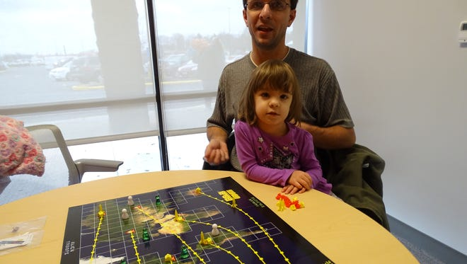 Jason Brown and daughter Jerrica show the board game 'Invasion.' The four-player dice game pits two players attempting to take down an alien mothership while alien forces attack Earth.