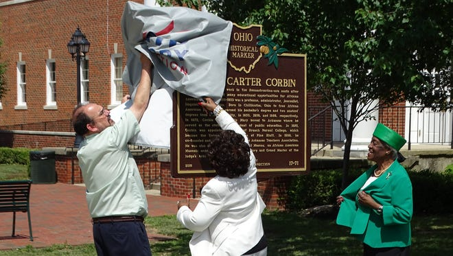 Ohio University Chillicothe Dean Martin Tuck, Rachel Foster, and Gladys Turner Finney remove the covering from a historical marker for Joseph Carter Corbin outside Bennett Hall on the OU-C campus Wednesday.