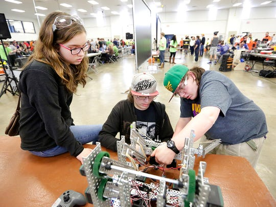 Isabella Elandt and William and Harley Schmidt of Waupaca work on their robot Saturday morning at the fourth annual Ishamon Harris Memorial VEX Robotics Competition Tournament held at the Fond du Lac Fairgrounds.