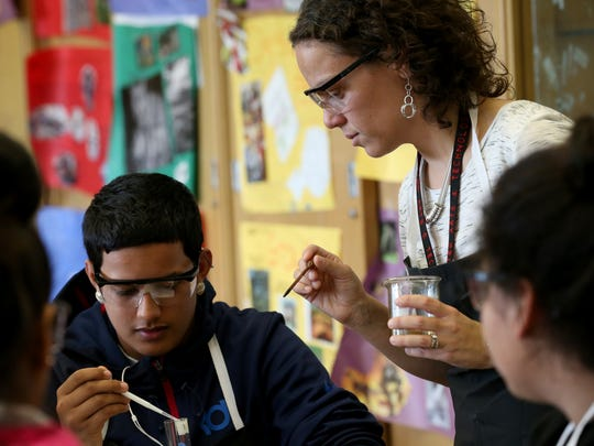 East High School science teacher, Elyse Boress, works with Ismael Ortiz Jr. on an experiment concerning diffusion across a cell membrane.