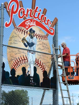 Erie artist Tom Ferraro installs a mural on Wednesday at Pontiac Field in Bayview Park. The mural celebrates Erie's baseball history and Negro League baseball greats like Sam Jethroe and Satchel Paige.