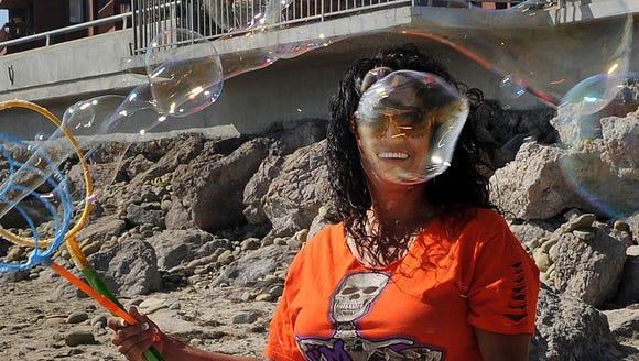 Pearl Orrantia makes bubbles on the beach near the