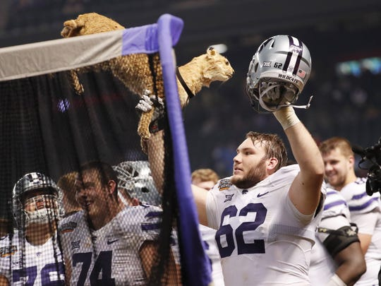 """Kansas State offensive lineman Tyler Mitchell (62) holds """"Phil the Bobcat"""" during the final minutes of their 35-17 Cactus Bowl win against UCLA at Chase Field in Phoenix, Ariz. December 26, 2017."""