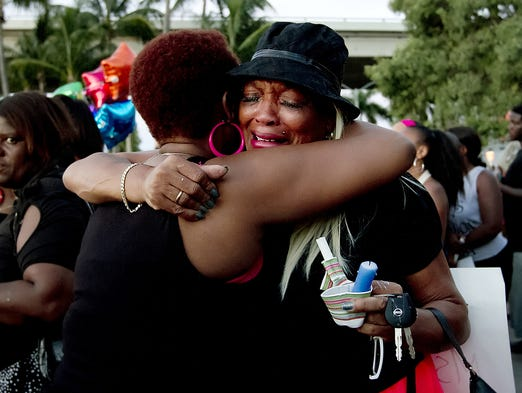 """Beatrice Loggins-Jones, left, comforts """"Mama"""" Carolyn Jackson during a candlelight vigil event in honor of Yazmin Shancez Sunday night at Centennial Park in downtown Fort Myers. Jackson is a long-time friend of the family."""