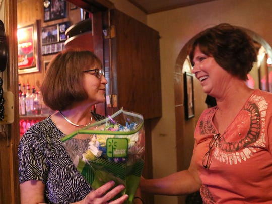 Jeannie Seubert, (L) reacts to Rae Spindler, of Rozellville and a long-time customer giving away flowers in the packed Buck-A-Neer Supper Club on its last night under current ownership, June 22, 2016.