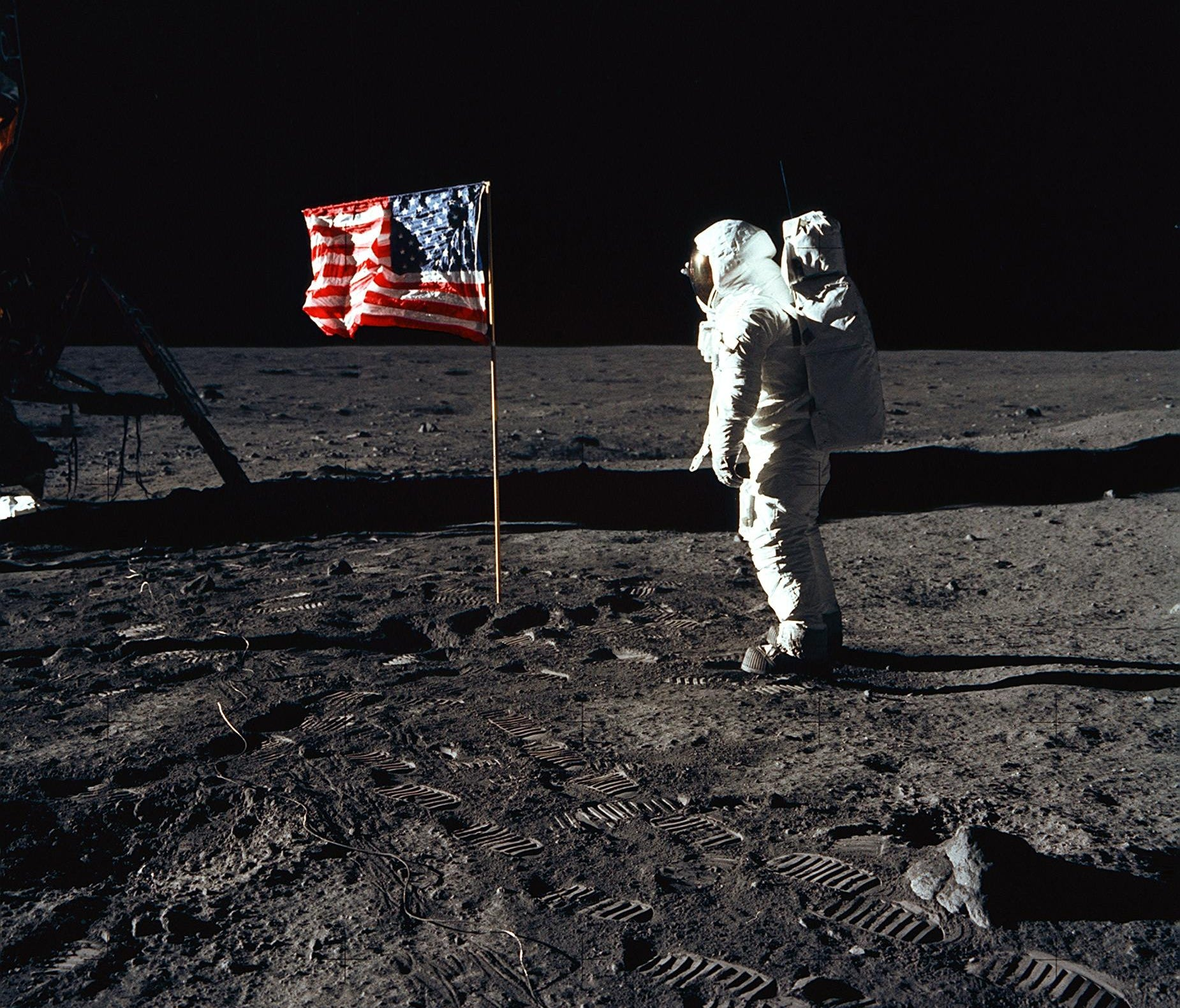 On July 20, 1969, astronaut Buzz Aldrin, lunar module pilot of the first lunar landing mission, posed for a photograph beside the deployed United States flag during an Apollo 11 moonwalk. The Lunar Module is on the left, and the footprints of the ast