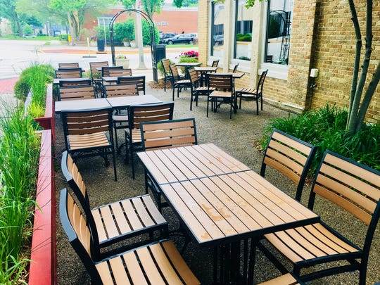 The patio at Moxie Food + Drink in Whitefish Bay is shaded by trees and is separated from E. Silver Spring Drive by shrubs and a gate, and N. Diversey Blvd. by planters holding ornamental grasses.