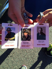 Participants show off the badges that they wore during the race to honor the fallen first responders of 9/11.