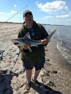 Michael Radigan holds a shark that he caught at South Bowers Beach on cut bunker.
