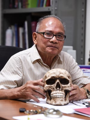 Dr. Aurelio Espinola, Guam chief medical examiner, is photographed at his desk with a replica of a human skull on Thrusday, Dec. 28, 2017.