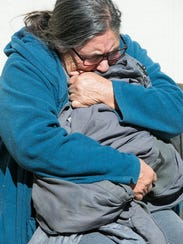 Raquel Lopez, 67, cries and grips the jacket of her