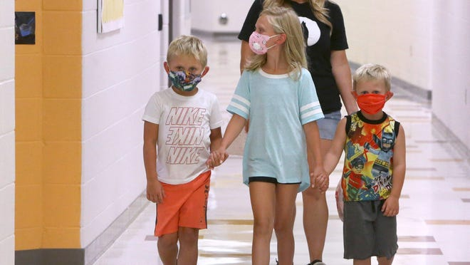 Jackson (left), Olivia (center) and Wyatt Schlimm hold hands as the siblings located classrooms during an open house at Sandy Valley Elementary School on Thursday August 13, 2020. Also visible behind them is their mother Julie Schlimm. Jackson is entering kindergarten, Olivia third grade and Wyatt is to begin preschool.