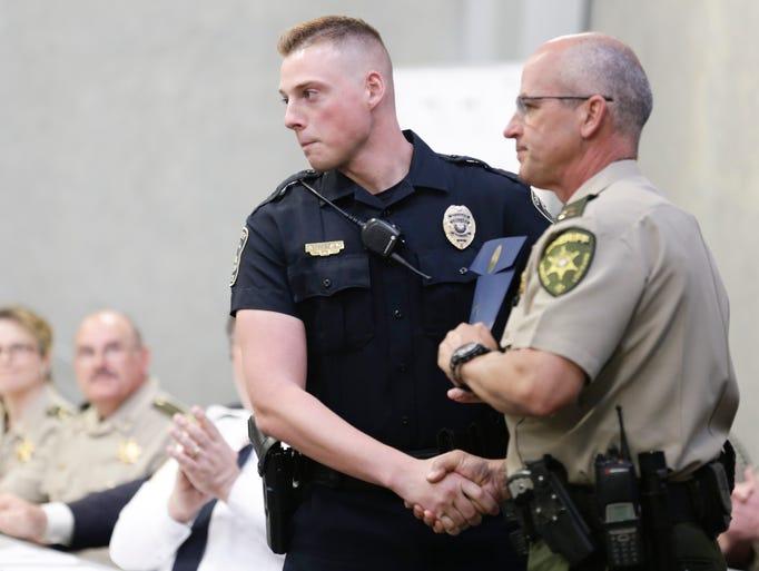 Crowley police graduate Aaron Bertrand accepts his
