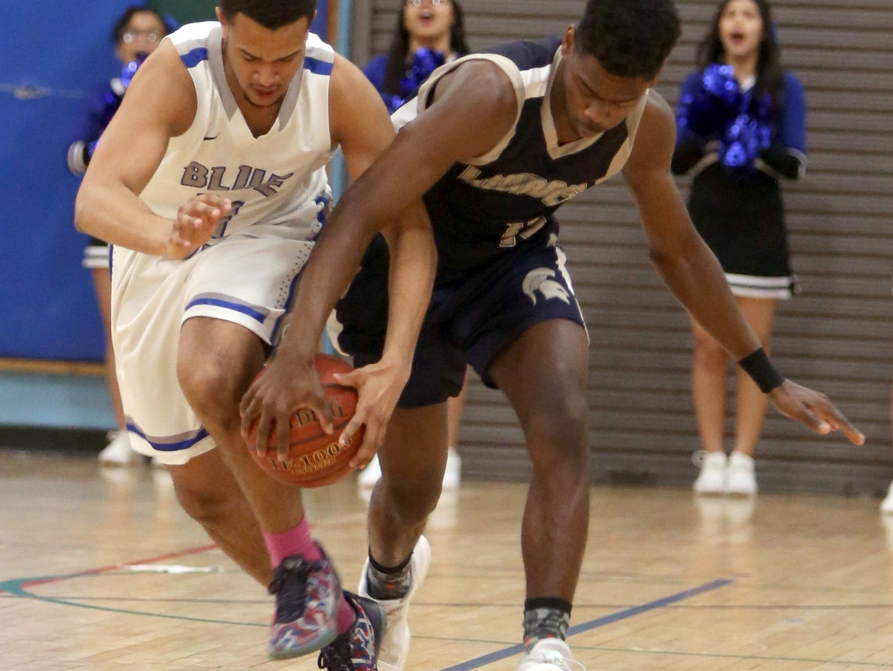 Jacob Vasquez-Mena of Saunders and Kevin Townes of Our Lady of Lourdes fight for the loose ball during a Class A quarterfinal basketball game at Saunders High School in Yonkers Feb. 23, 2017. Lourdes defeated Saunders 58-57.