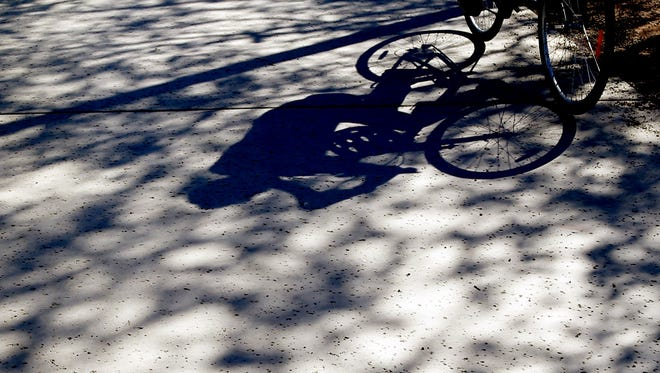 A bicycle rider casts a shadow on the shaded pavement on March 13, 2017, at Desert Breeze Park in Chandler. Phoenix reached 92 degrees, tying the heat record for March 13 that was set in 1972. Highs are expected to reach the mid-90s by the weekend.