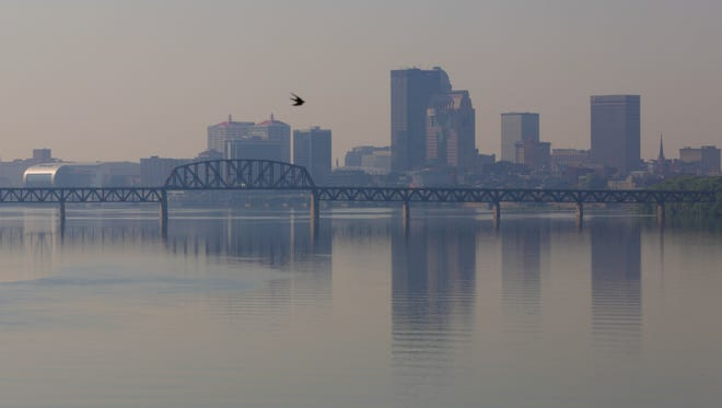 A bird flies over the Ohio River on a hazy July day in Louisville.