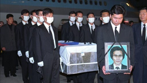 FILE - In this Oct. 5,1996 file photo, government officers carry a portrait and a coffin containing South Korean Choi Duk-kun, a South Korean diplomat stationed in the eastern Russian city of Vladivostok, upon the body's arrival at Gimpo International Airport in Seoul, South Korea. Choi was found dead in front of his apartment in 1996. He had head wounds, but his passport and money were still in his pockets.