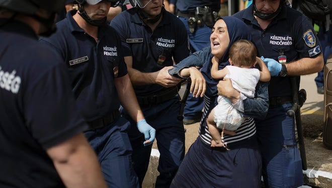 A migrant family is arrested by police after their train coming from Budapest and heading to the Austrian border was stopped in Bicske, west of the Hungarian capital on Sept. 3, 2015.