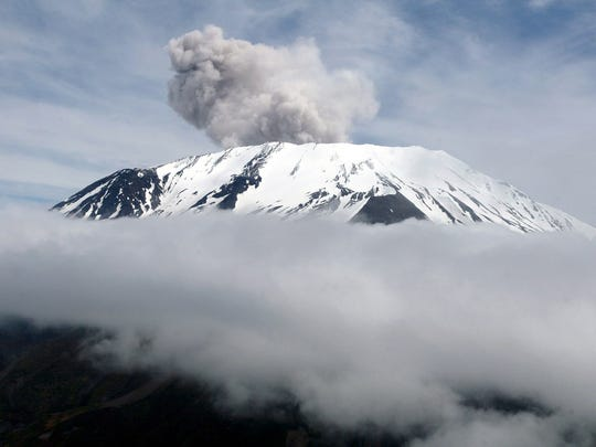 Dust and ash flow out of Mount St. Helens after hot rocks fell off the new dome being built inside its crater, Thursday, May 12, 2005.