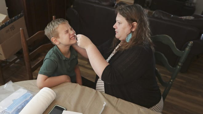 Mendy McNulty swabs the nose of her son, Andrew, 7, Tuesday, July 28, 2020, in their home in Mount Juliet, Tenn. Six thousand U.S. parents and kids are swabbing their noses twice a week to answer some of the most vexing mysteries about the coronavirus. The answers could help determine the safety of in-class education during the pandemic.