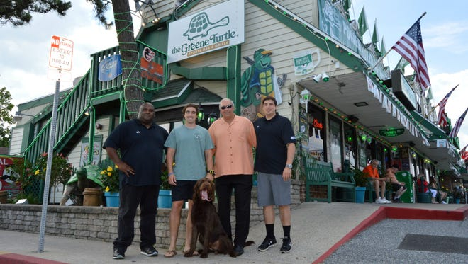The current faces of the original Greene Turtle on 116th Street in Ocean City — operations manager Shawn Sturgis, Stephen Pappas, Greene Turtle founder Steve Pappas, Jason Pappas, and Leo the 10-month-old labradoodle.