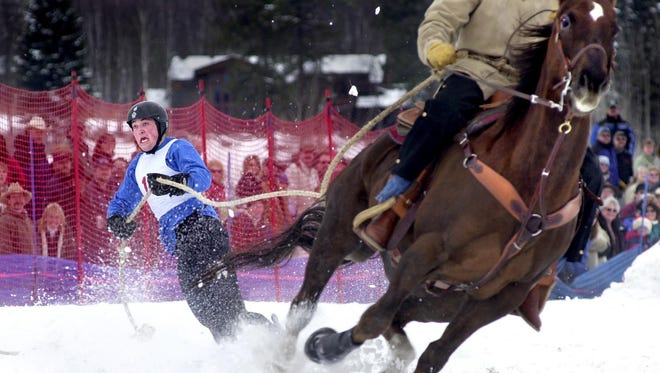 Novice skijoring competitor Craig Peters runs the course at the 2003 Whitefish Winter Carnival. The competition drew nearly 70 teams of horses, riders and skiers.