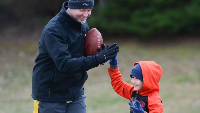 Brent Kose gives his son Dylan, 6, a high-five after his touchdown at the 12th annual Father Son Bowl in Franklin on Saturday, Feb. 3, 2018.