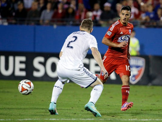 FC Dallas midfielder Mauro Diaz (10) makes a pass to Tesho Akindele past Vancouver defender Jordan Harvey (2) in the first half of an MLS playoff soccer match, Wednesday, Oct. 29, 2014, in Frisco, Texas. Akindele scored off the pass from Diaz. (AP Photo/Tony Gutierrez)