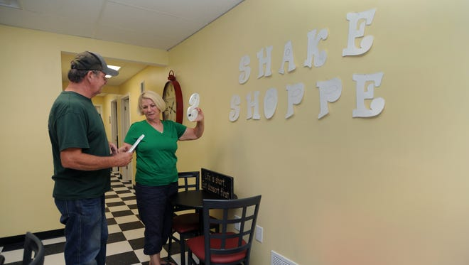 Connie McCollister, and her husband, Kenneth McCollister, owners, hang letters on the wall Thursday at Pleasant Valley Shake Shoppe.