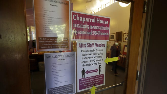 Signs advising of COVID-19 symptoms and social distance are posted on the front door of Chaparral House in Berkeley, Calif., Friday, July 10, 2020. For months, families have pined to see their loved ones in California's skilled nursing facilities, which have been shut down to outside visitors to keep out the coronavirus. California's health authorities recently issued guidance for visits to resume at these facilities, but so far, few appear to be happening as infection rates surge in many communities.