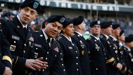 Washington National Guard members wait in an end zone to take a re-enlistment oath before an NFL football game between the Seattle Seahawks and Minnesota Vikings late last year. Washington and other states view the Guard as a natural fit to counter cyberattacks.