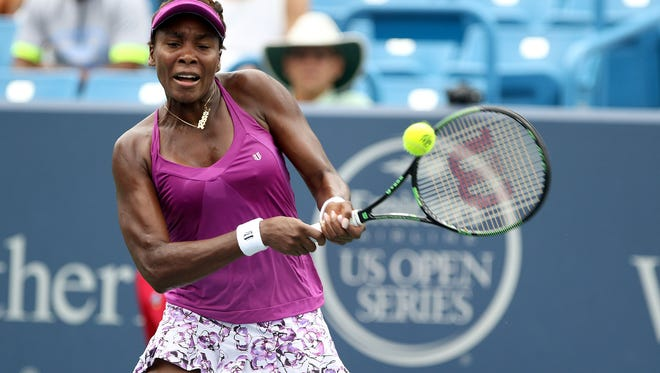 Venus Williams makes a hit to Zarina Diyas on Center Court during the Western and Southern Open at the Lindner Family Tennis Center in Mason Monday August 17, 2015.
