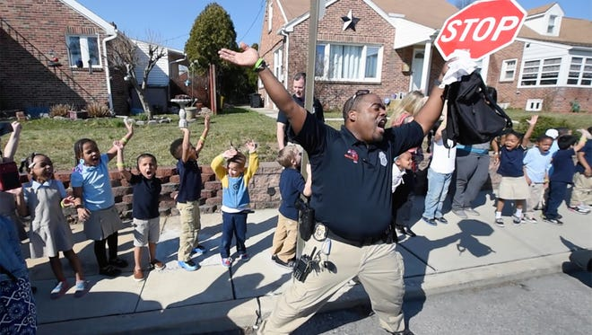 Officer Michael Muldrow helps Devers K-8 School pre-kindergarten students practice yelling 'no' to a stranger who tries to grab them on the street as school officers lead the students on a safety walk.