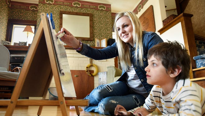 Personal caregiver Rachel Wallece works with Elliott Gilbert, 8, after school Wednesday, April 13, on his spelling words.