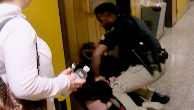 In this Monday, Jan. 8, 2018, image made from a video provided by KATC-TV, middle-school English teacher Deyshia Hargrave is handcuffed by a city marshal after complying with a marshal's orders to leave a Vermilion Parish School Board meeting in Abbeville, La., west of New Orleans. Hargrave was removed from the school board meeting, forcibly handcuffed and jailed after questioning pay policies during a public comment period.