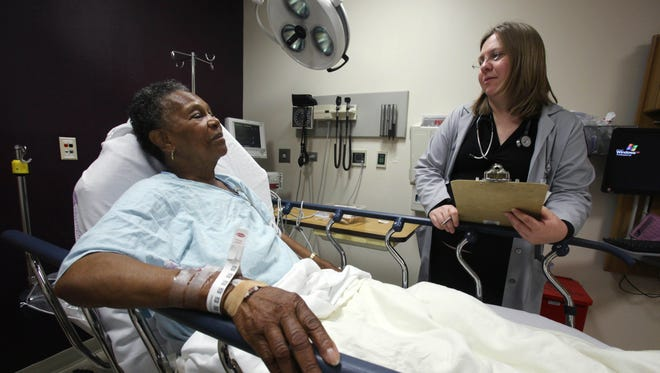 Physician Rebecca Parker talks to 74-year-old patient Charlene Ladner in the emergency room of Chicago's Advocate Trinity Hospital. An influx of newly insured patients has increased the number of paid admissions to hospitals, which cuts hospitals uncompensated care costs.