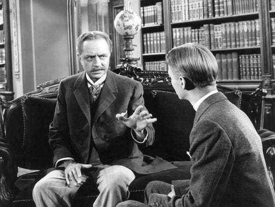 Jimmy Lydon looks on at William Powell in a scene from