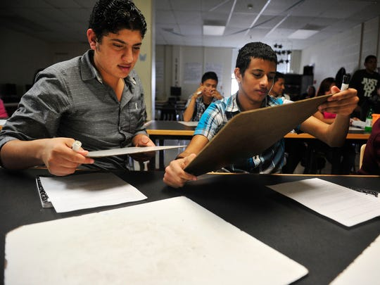 Mina Mikhil, 18, and Beshoy Estefanous, 16, take a quiz in an English language learner class at Glencliff High School in Nashville on Oct. 29, 2015.