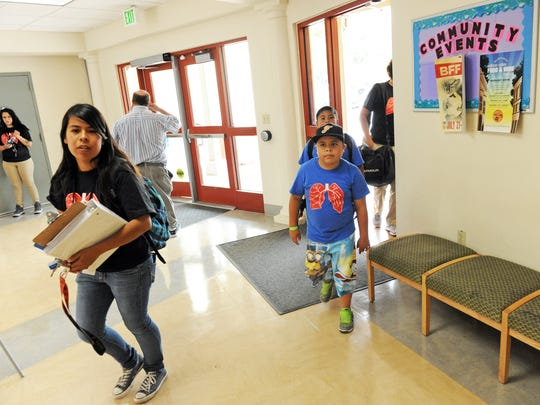 Central Coast YMCA Counselor Briana Avila leads kids in the Asthma Camp toward the pool on Wednesday.