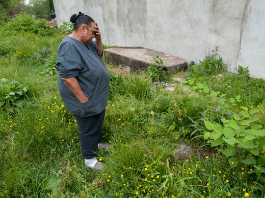 Barbara Wyatt is overcome with emotion as she views  the condition of the gravesite of her son, Abdul Jabbar Wyatt, at Evergreen Cemetery in Camden.  The cemetery is overgrown and littered with trash and debris.