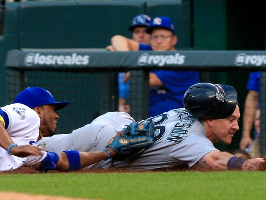 Seattle Mariners' Dan Robertson (99) is tagged out by Kansas City Royals shortstop Alcides Escobar (2) after getting caught in a rundown during the second inning of a baseball game at Kauffman Stadium in Kansas City, Mo., Thursday, July 7, 2016. (AP Photo/Orlin Wagner)