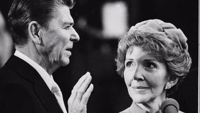 Nancy Reagan proudly watches as her husband Ronald Reagan takes the oath of office at the Capitol in Washington in this Jan. 20, 1981, file photo.