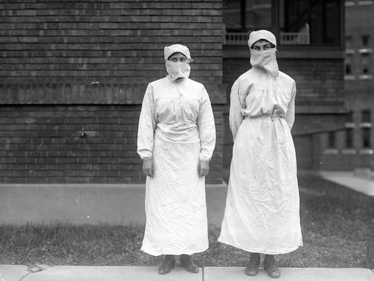 Two women wearing clothing aimed to prevent the spread of infection during the flu epidemic stand outside Rochester General Hospital in October 1918. The gowns, tied at the waist with cords, have long sleeves and reach their ankles. Cloth head wrappings cover their hair and the masks over their faces are made of thick cloth.