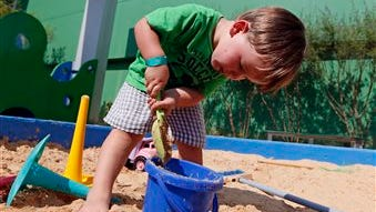 Brayden Squyres, 2, of Brandon, concentrates on filling his bucket with sand in the Desert Island Exploration sand pit at the Mississippi Children's Museum in Jackson, Miss. The interactive hands-on facility promotes literacy, health and nutrition, learning the state's heritage and exploration of its cultural arts and key economic industries in a fun setting.