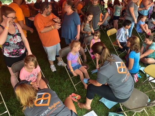 Volunteers wash every child's feet before they receive new socks and shoes during Project Big Love on Saturday, July 30, 2016 in Mont Alto, Pa.