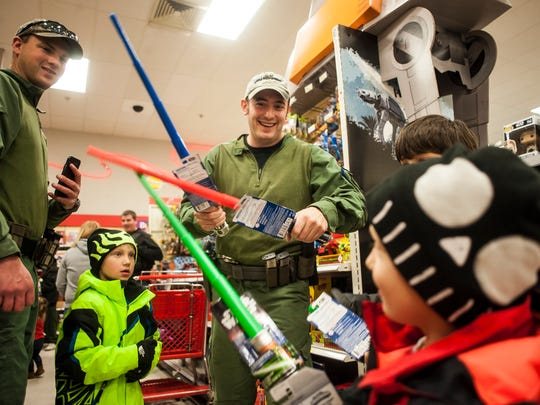 Adam Hunt plays lightsabers with Brentlee Dezort, 4, during Shop with a Cop at Target Tuesday, Dec. 13, 2016.