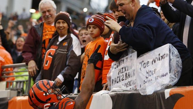Cincinnati Bengals running back Joe Mixon (28) hands a fan a football after scoring a touchdown against the Cleveland Browns last December in Paul Brown Stadium.