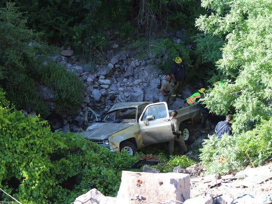Truck rolls down embankment