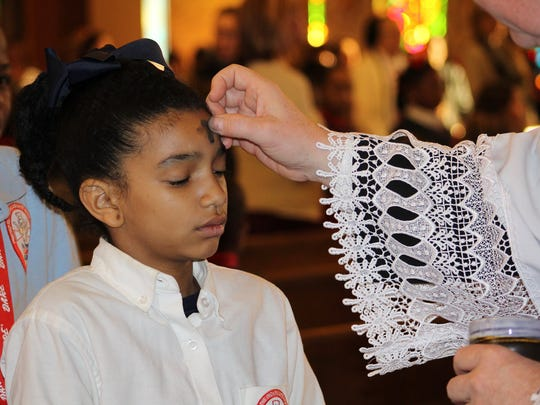 Kennedi Johnson, a fourth-grader at St. Frances Cabrini School, receives ashes Wednesday morning at Mass.